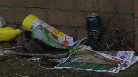 Litter on a street, including a shoe, bottle of bleach and alcoholic drink can.