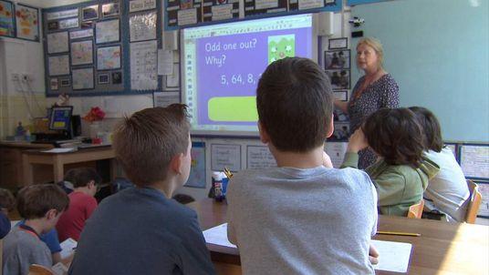 A Teacher And Children Taking Part In A Maths Class