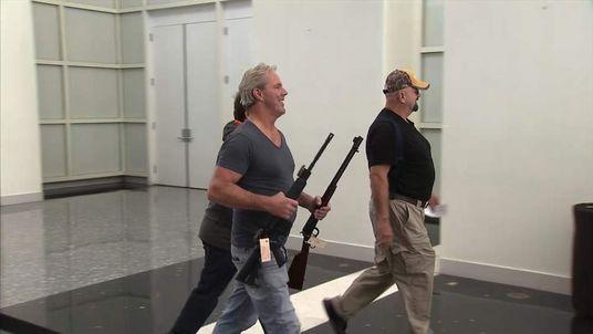 A man carries guns at a gun show in California.