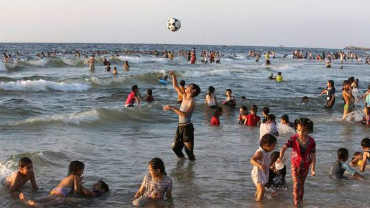 Palestinians play in the Mediterranean Sea off the coast of Gaza City