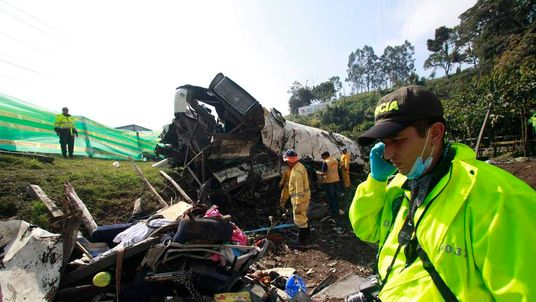 A police officer near the wreckage of a bus