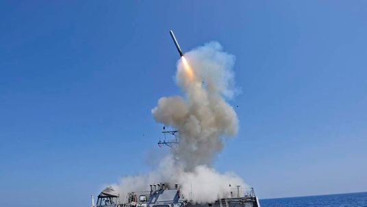 US Navy guided-missile destroyer USS Barry launching a Tomahawk cruise missile