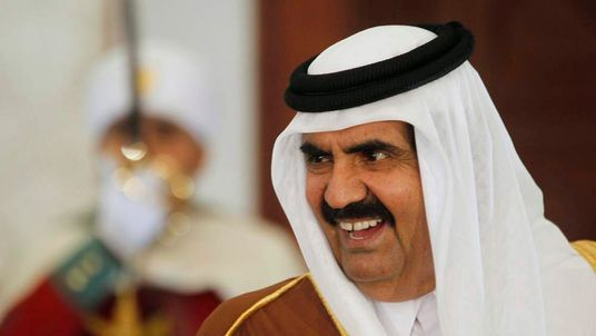 Qatar's Emir Sheikh Hamad bin Khalifa al-Thani smiles upon his arrival at Houari Boumediene Airport in Algiers