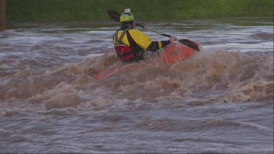 A man kayaks in a swollen river