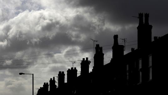 Rain clouds gather behind a row of terraced houses