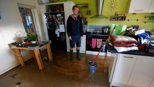 James Alcock stands in his kitchen after flood waters receded in St Asaph, north Wales