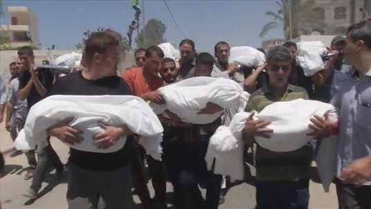 Hundreds march carrying the bodies of those killed in Gaza offensive