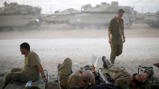 Israeli soldiers rest in a staging area near the border with the northern Gaza Strip