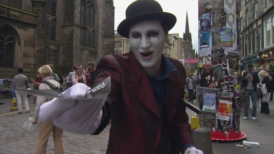 An artist hands out leaflets at the Edinburgh Fringe