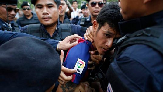 A man is detained by the police after a confrontation during a protest against military rule in Bangkok