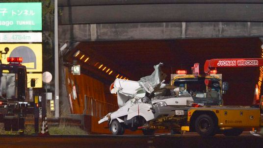 A damaged truck is towed away from the Sasago Tunnel on the Chuo Expressway