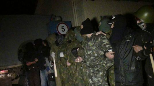 Pro-Russian protesters stand in formation near a Ukrainian military base in Mariupol
