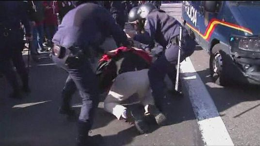 Police arrest an anti-austerity protester in Madrid, Spain