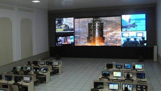North Korean scientists work as a screen shows the Unha-3 (Milky Way 3) rocket being launched from a launch pad at the West Sea Satellite Launch Site, at the satellite control centre in Cholsan county, North Pyongan province