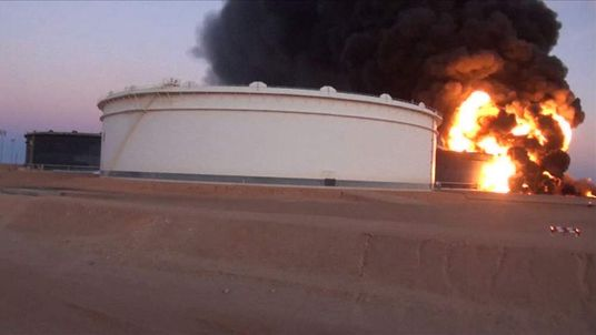 Black smoke plumes rising from burning oil storage tanks at Al-Sidra oil facility