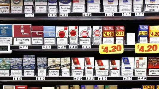 Shopkeeper Picking Cigarettes Off Shelf In Shop