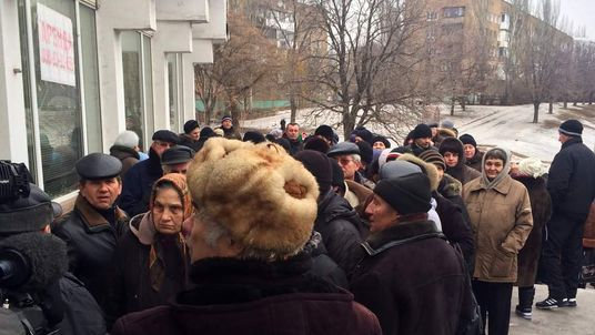 Residents in Donetsk queue for aid.