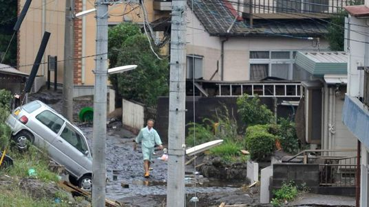 A man walks along a road covered in mud after heavy rains fell at Kumamoto city in Japan's southern island of Kyushu