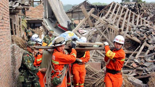 Rescuers carry out an elderly person from a collapsed house after a strong 6.6 magnitude earthquake hit Qingren township of Lushan county