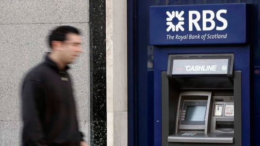 A pedestrian passes a Royal Bank of Scotland cash machine in London