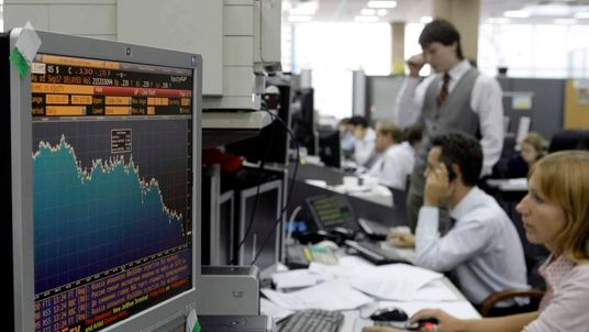 Traders look at screens at a bank in Moscow