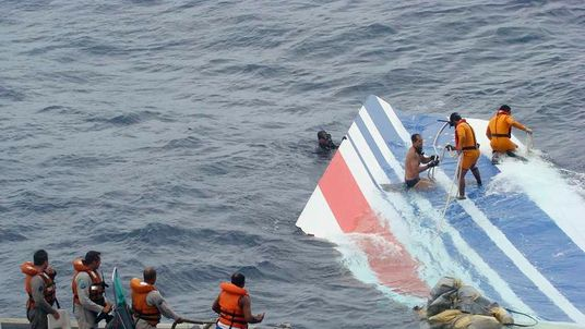 Brazilian Navy sailors pick a piece of debris from Air France flight AF447 out of the Atlantic Ocean