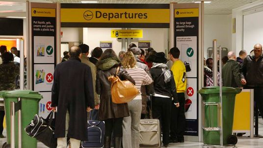 Passengers queue to go through security checks at the departure gate at Gatwick Airport in southern England