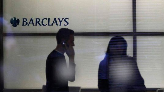 People walk inside Barclays Bank's headquarters in the financial district of Canary Wharf, east London