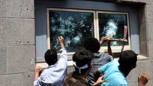 Protesters break windows at the U.S. embassy in Sanaa September 13, 2012. Hundreds of Yemeni demonstrators stormed the U.S. embassy in Sanaa on Thursday in protest against a film they consider blasphemous to Islam, and security guards tried to hold them off by firing into the air.