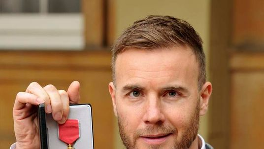 Take That singer Gary Barlow holds his OBE, for services to the entertainment industry and to charity, which was awarded to him by Queen Elizabeth in London