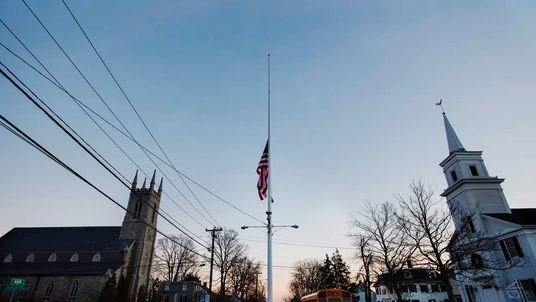 A U.S. flag flies at half staff as a school bus drives past in the town of Newtown, Connecticut after a shooting nearby at Sandy Hook Elementary School