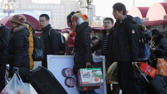 A woman holding her wedding photo arrives at Beijing Railway Station