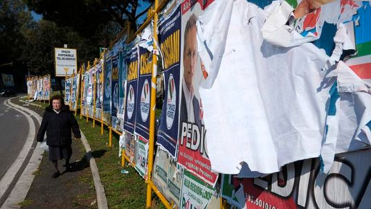 A woman walks next to electoral posters in Rome