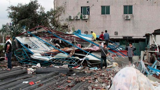 Labourers clean up the debris of a shed which was destroyed by a thunderstorm and hail in Dongguan