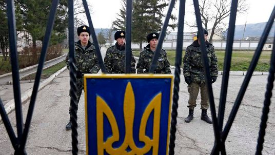Ukrainian servicemen stand guard outside a military unit in Perevalnoye outside Simferopol