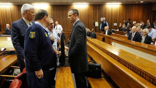 Oscar Pistorius speaks to his legal team from the dock ahead of the second day of the trial of the Olympic and Paralympic track star at the North Gauteng High Court in Pretoria