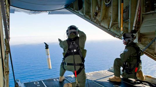 RAAF Loadmasters, Sergeant Roberts and Flight Sergeant Mancey, launch a 'Self Locating Data Marker Buoy' from a C-130J Hercules aircraft in the southern Indian Ocean during the search for missing MH370