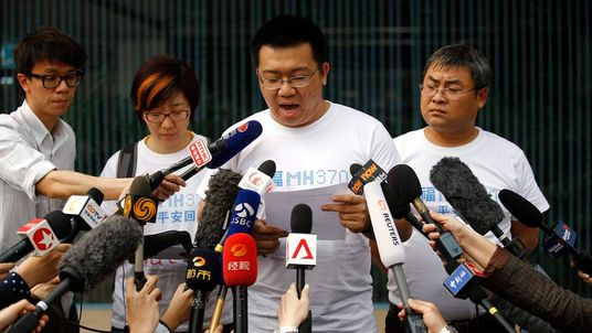 Wang, a family member of a passenger onboard Malaysia Airlines MH370, reads a statement to journalists outside Lido Hotel in Beijing