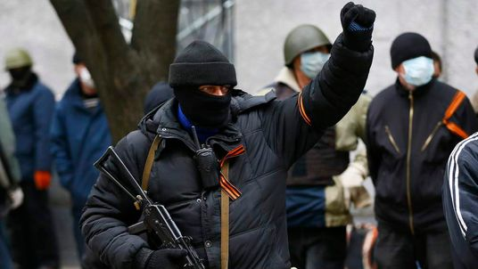 An armed man gestures in front of the police headquarters in Slaviansk