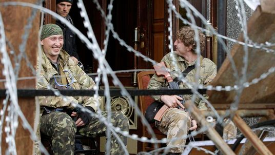 Pro-Russian armed men sit at the entrance to the regional government headquarters in Luhansk