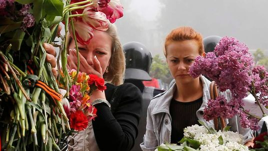 Women bring flowers in memory of people killed in recent street battles