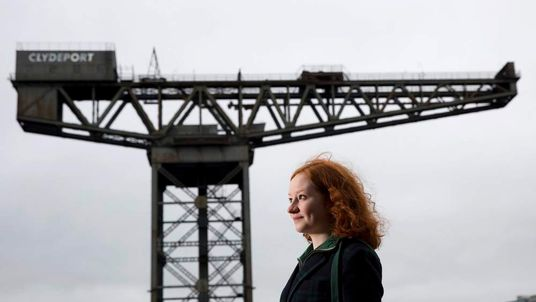 Amy McKenzie Smith poses for a photograph on the banks of the River Clyde with Finnieston Crane in the background in Glasgow