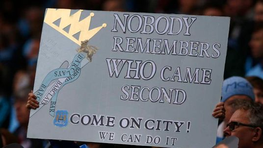 A Manchester City fan holds a banner as his team takes on West Ham United during their English Premier League soccer match in Manchester