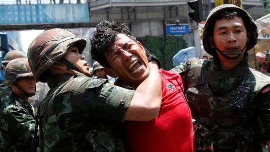 Soldiers detain a protester against military rule, at a shopping district in central Bangkok