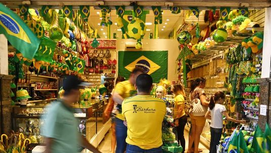 People pass a souvenir shop in the city of Fortaleza on June 9