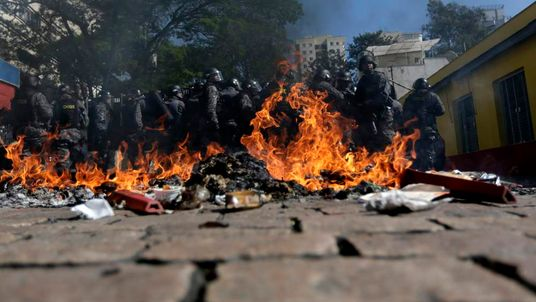 Riot policemen stand behind burning rubbish during a protest against the 2014 World Cup in Sao Paulo