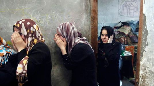 Relatives of eight Palestinian members from al-Haj family, who medics said were killed in an early morning air strike that destroyed at least two homes, mourn during their funeral in Khan Younis