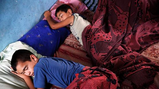 Palestinian boys sleep at a United Nations school, where people who fled heavy Israeli shelling in the Shejaia neighbourhood sought refuge during fighting, in Gaza City