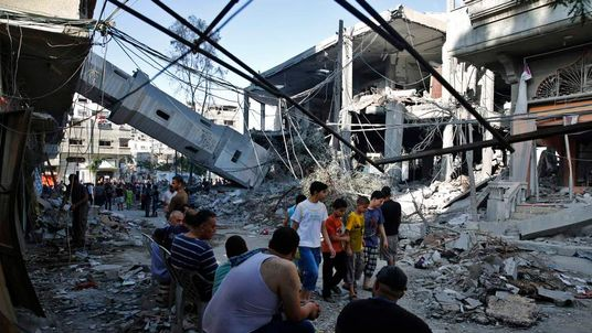 Palestinians gather near the minaret of a mosque that police said was destroyed by an Israeli Air strike in Gaza City
