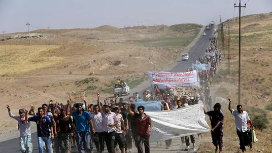 Displaced people from the minority Yazidi sect, who fled  the violence in the Iraqi town of Sinjar, demonstrate at the Iraqi-Syrian border crossing in Fishkhabour